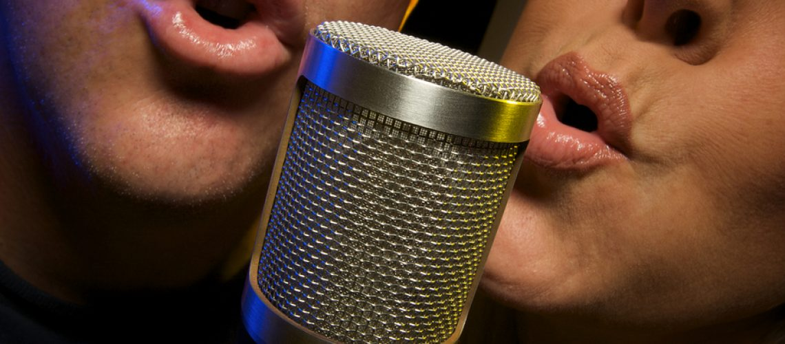 Couple Singing a Duet into a Microphone.